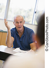 Mature male student gesturing in class