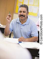 Mature male student raising hand in class