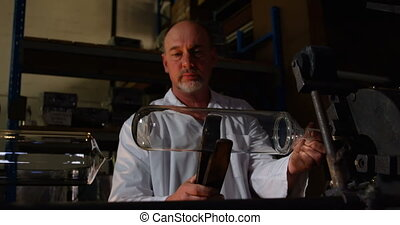 Mature male worker examining chemglass in glass factor. Mature male worker holding chemglass with tong 4k