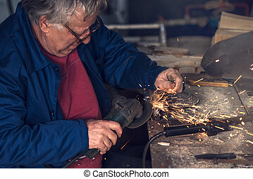 Mature male worker grinding metal in workshop
