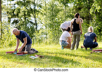 Mature Man And Friends Playing With Building Blocks On Field