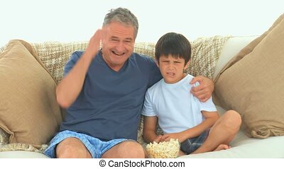 Mature man and his grandson watching a match on tv in the...