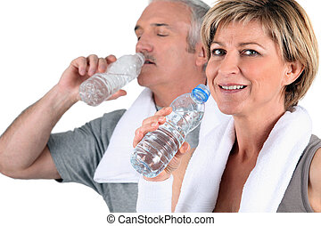 Mature man and woman in sportswear drinking water