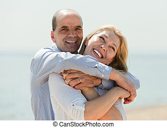 Mature man and woman together against sea
