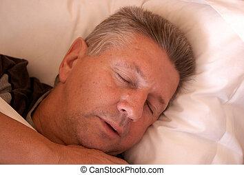Mature man asleep in bed