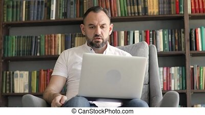 Mature man boss online on video link swears at worker on bookshelves background in home office. Remote work of teacher, professor, businessman, manager, boss, leader at computer. Distant work concept.