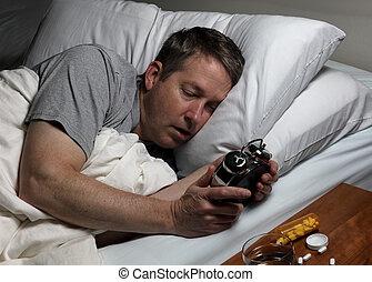 Mature man cannot fall asleep thus looking at time on alarm clock