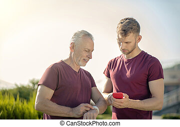 Mature man checking smartwatch with bearded male holding smartphone