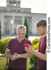 Mature man checking smartwatch with young male holding smartphone