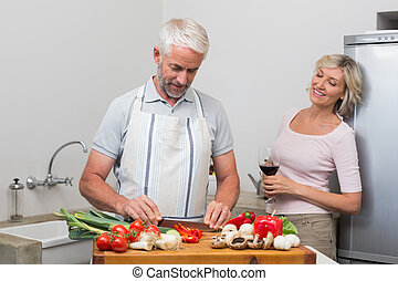 Mature man chopping vegetables while woman with wine glasses in the kitchen at home