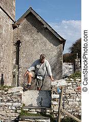 Mature man climbing over a wall