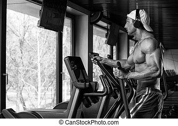 Mature Man Doing Aerobics Elliptical Walker In Gym -...