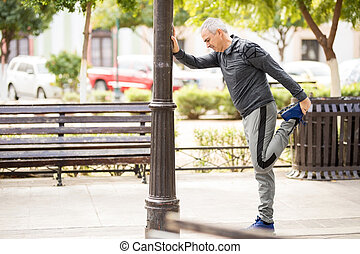 Mature man doing some leg stretches in the city