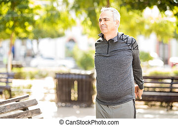 Mature man doing warm up exercise in park