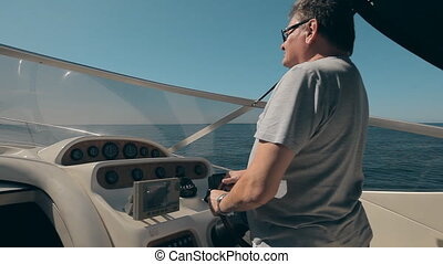 Mature man drives the yacht