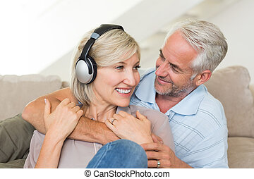 Mature man embracing woman from behind on sofa