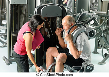 Mature man exercising with personal trainer - Mature man...