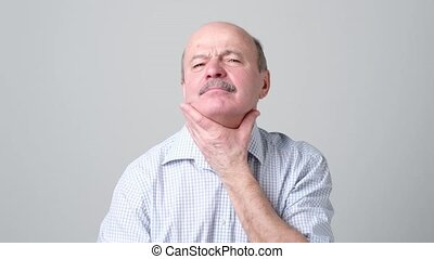 Mature man has a terrible pain in throat because of flu. He...