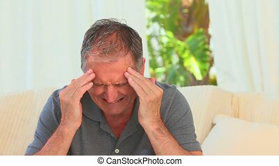 Mature man having a huge headache