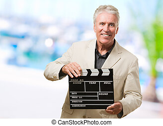 Mature Man Holding Clapper Board