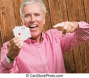Mature Man Holding Playing Cards