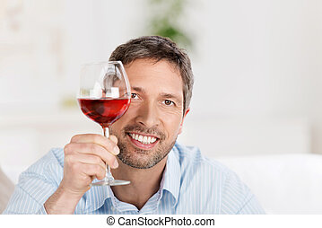 Mature Man Holding Wineglass At Home - Portrait of happy...