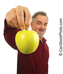 Mature man holds an apple by its stem