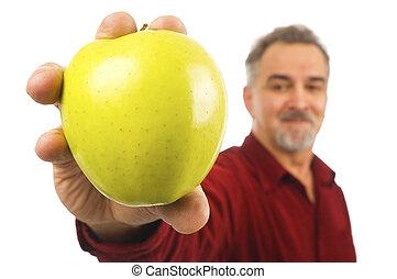 Mature man holds an apple.