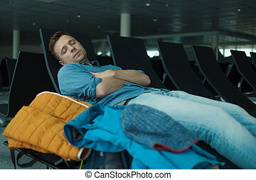 Mature man in airport sleeping on a bench