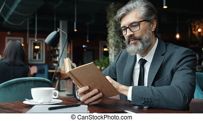 Mature man in glasses and suit reading book at table in ...