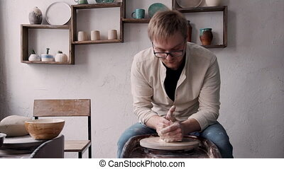 Mature man in glasses is sitting and holding clay on wheel...