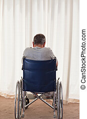 Mature man in his wheelchair with his back to the camera at...
