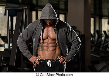 Portrait Of A Physically Fit Man In Hoodie - In Modern Fitness Center - Showing His Six Pack