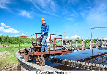 Mature man in protective hardhat and workwear standing on waste water treatment unit