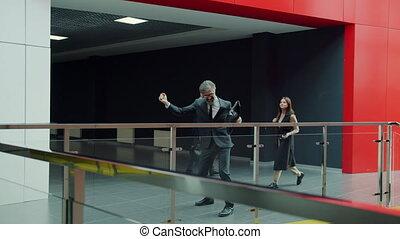 Mature man in suit dancing in office hallway enjoying ...