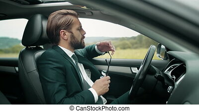 Mature man in business suit and eyewear rubbing his eyes because of long riding car. Bearded person feeling tired on road. Concept of success and overwork.