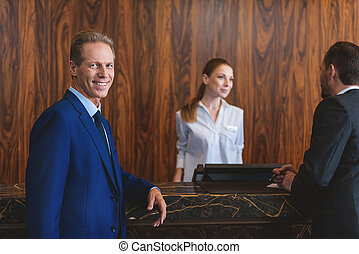 Mature man in suit waiting in hotel