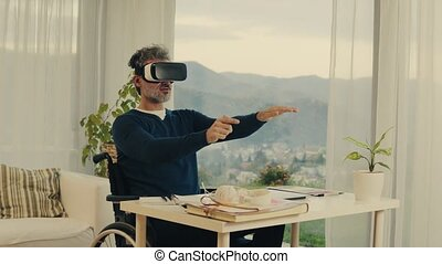 Mature man in wheelchair with VR goggles in home office. -...