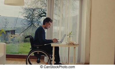 Mature man in wheelchair working in home office. - Handsome...