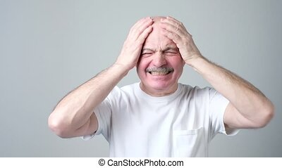 Mature man in white tshirt with closed eyes touching his...