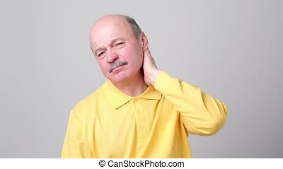 Mature man in yellow tshirt with closed eyes touching his...