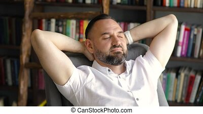 Mature man is dreaming resting in armchair in library with ...