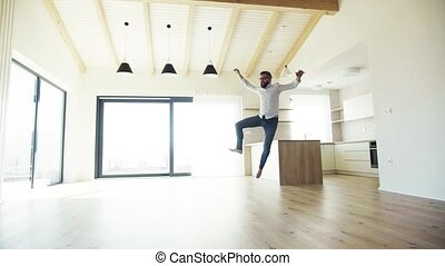Mature man jumping in unfurnished house, moving in new home concept.