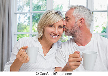Mature man kissing woman while having coffee in bed