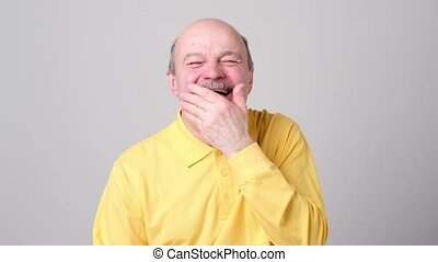 Mature man laughing and covering his mouth with hand over...