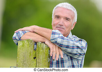 mature man leaning on post