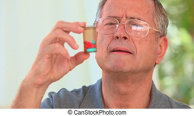 Mature man looking at his pills