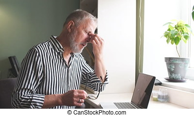 mature man looking exhausted while sitting at his laptop and holding his glasses in hand