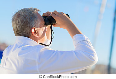 Mature Man Looking Through Binocular