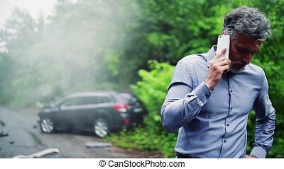 Mature man making a phone call after a car accident, smoke...
